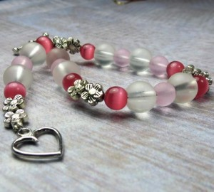 Pink beads of all kinds in a bracelet ending with a heart