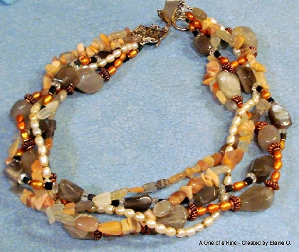 This Collar style necklace features five beaded strands filled with moonstones pearls and more