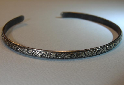 Sterling silver cuff bracelet with patterned leaf design and patina